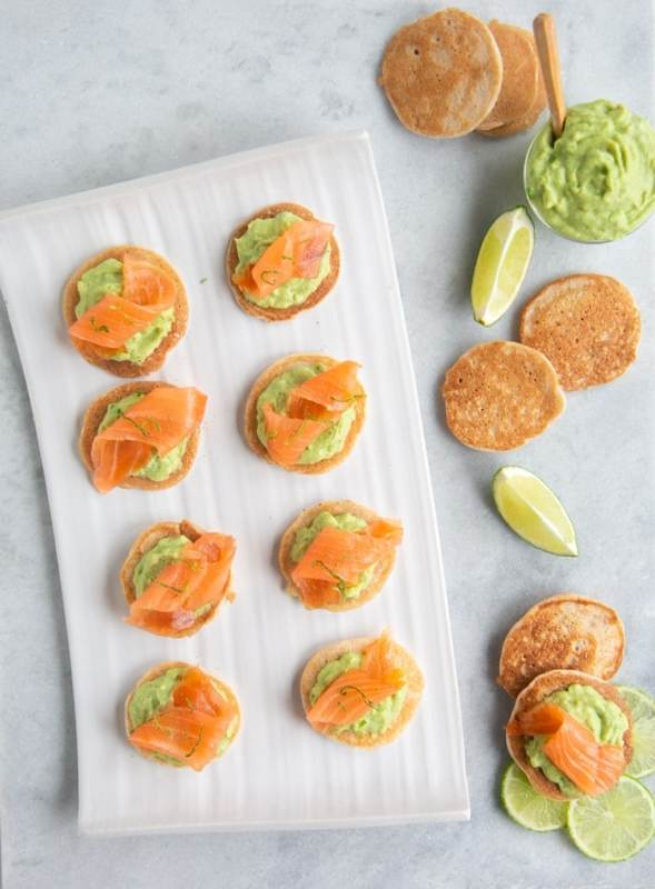 gluten-free blini with avocado cream and smoked salmon on white plate next to avocado cream in bowl, plain blini and slices of lime