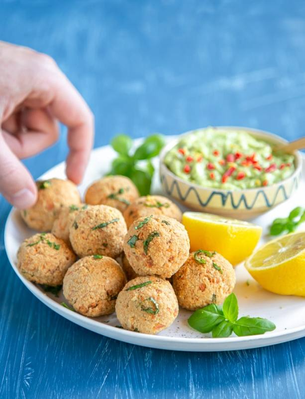 baked salmon meatballs on white plate served with halved lemon, basil leaves and avocado cream in a small pot, hand picking up a meatball in the background