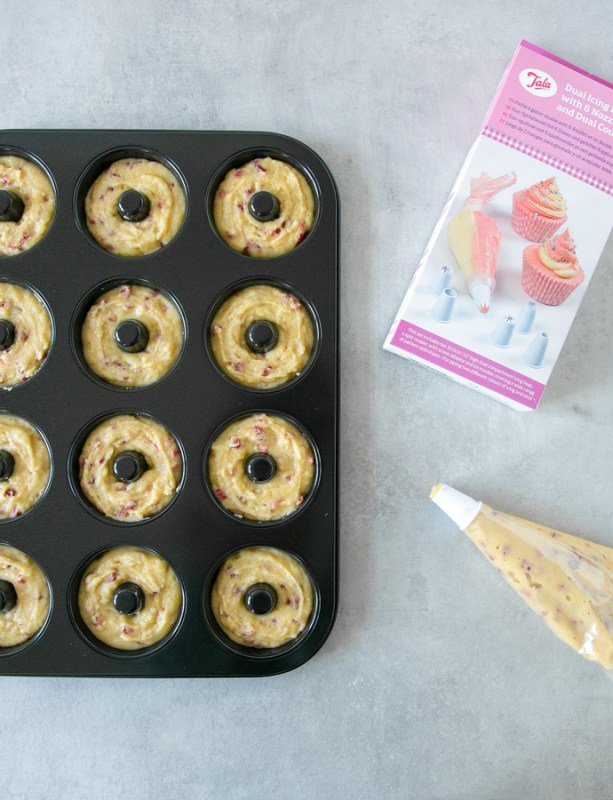 doughnut pan filled with batter, next to a piping bag filled with batter and Tala box of the piping bag