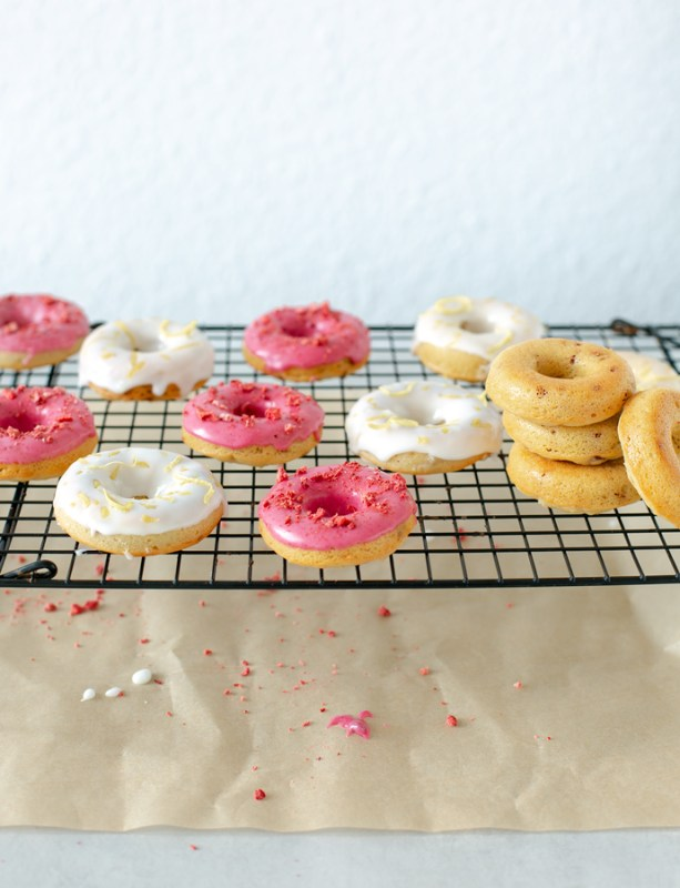 white and magenta glazed strawberry-Lemon gluten-free baked doughnuts on a cooling rack, baking paper underneath