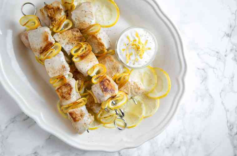 lemon chicken skewers and small pot with yogurt dip and lemon slices onto white serving plate
