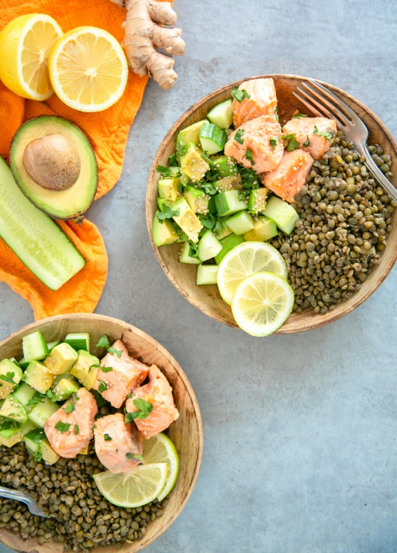 on the top left orange napkin with half cucumber, half avocado, halved lemon and ginger root on top. On the down left side, the same salmon, lentils and veggie dish on a wood plate