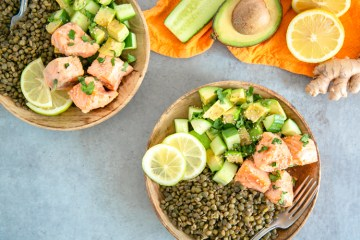 on the top right side an orange napkin with half cucumber, half avocado, halved lemon and ginger root on top. On the top left side, the same salmon, lentils and veggie dish on a wood plate