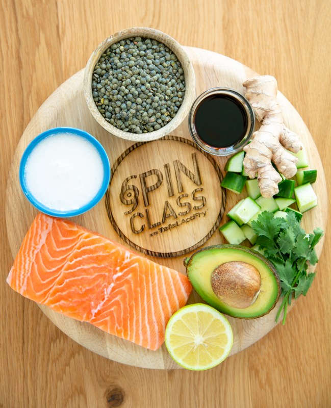 wood board branded with the Spin class by tefal actifry writing, on top of it a salmon fillet, small blue pot with coconut milk, small wood pot with green lentils, small glass pot with soy sauce, ginger root, cubed cucumber, coriander leaves, half avocado and half lemon.