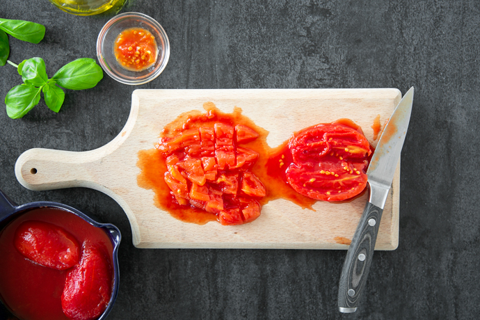 chopped tomato and halved tomato with a knife on a wood chopping board, on the left side canned tomatoes in a blue bowl, and on the top left side basil leaves, and a small bowl with the seeds removed from the tomatoes.