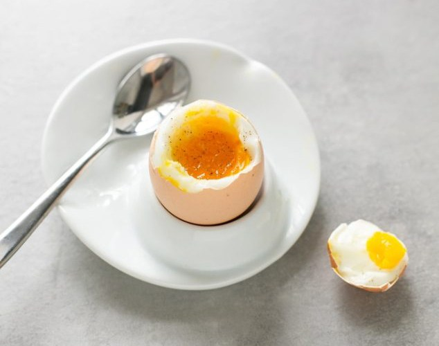 soft boiled egg on a plate next to a spoon