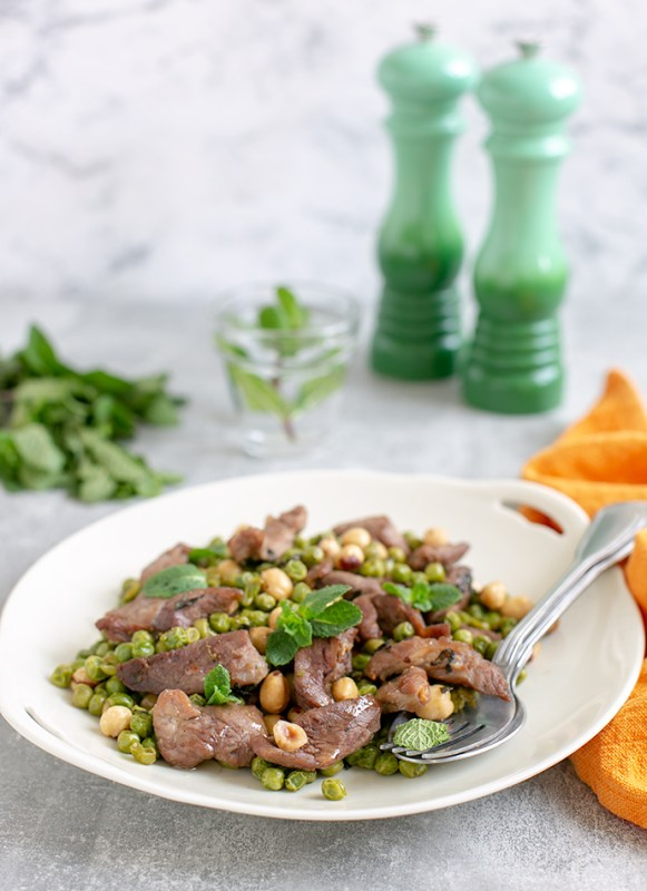 Air Fryer Mint Lamb with Toasted Hazelnut and Peas on a white serving dish, salt and pepper mills in the background together with a glass of water and extra mint leaves.