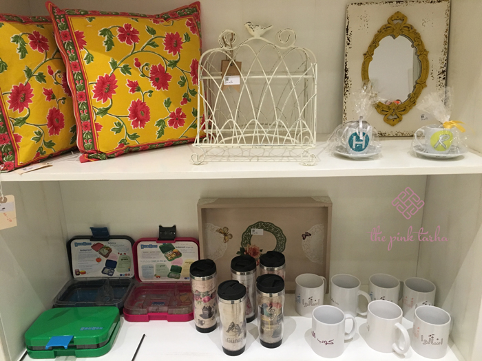 Assortment of lunch boxes, tumblers, mugs, frames, and pillows.