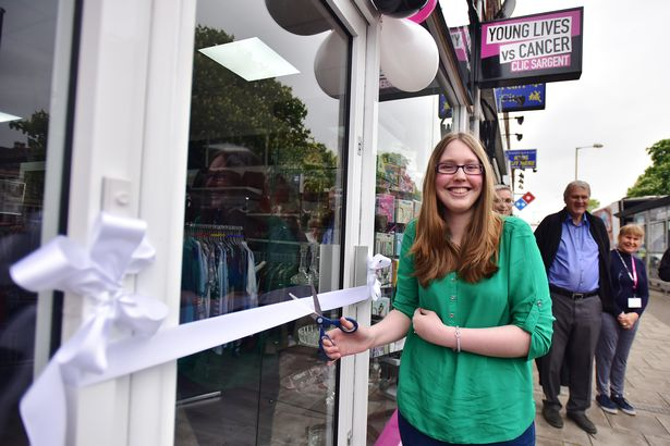 Melissa who had cancer as a child cutting the ribbon to reopen the Fishponds clic shop
