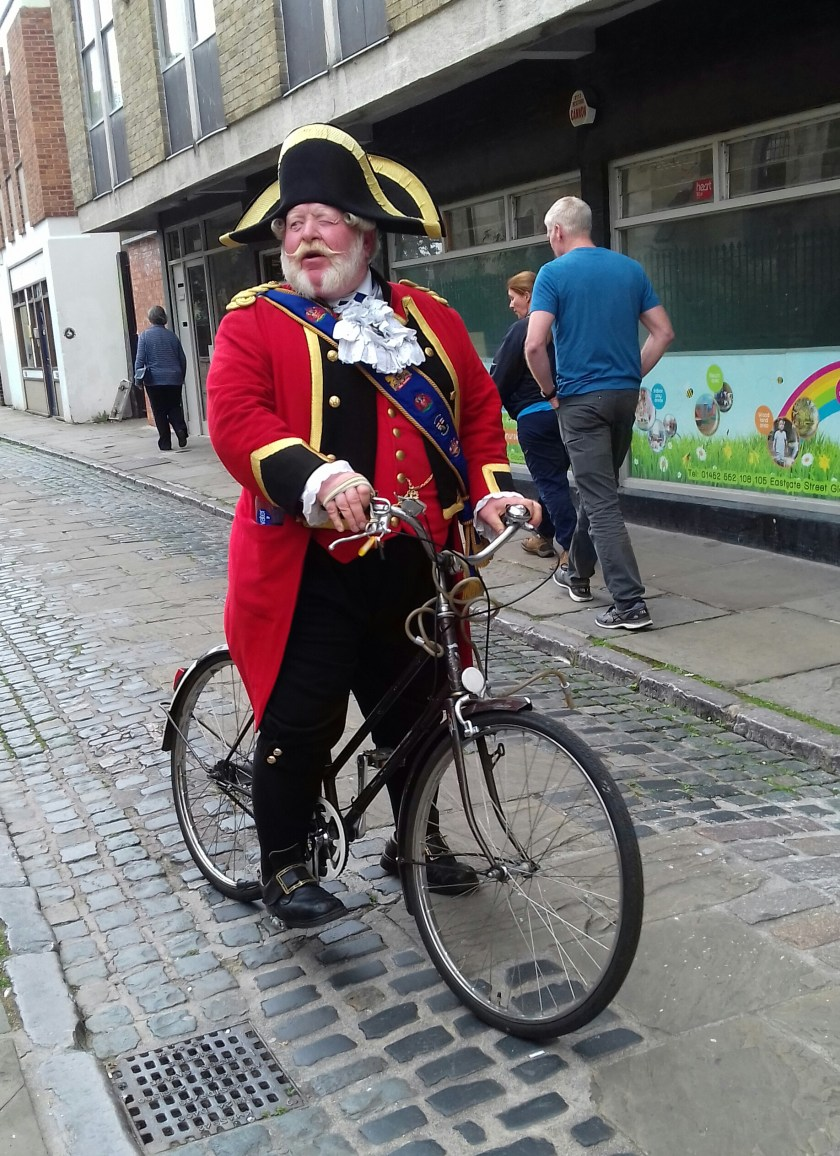 A man in red coat and sash riding a bicycle