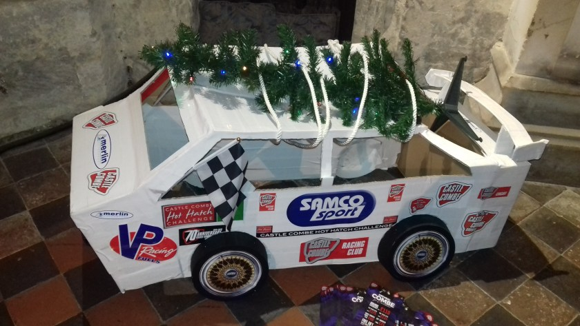 A model racing car with a Christmas tree on the roof