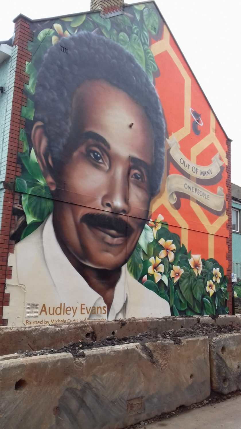 A portrait of Audley Evans on the side of a house