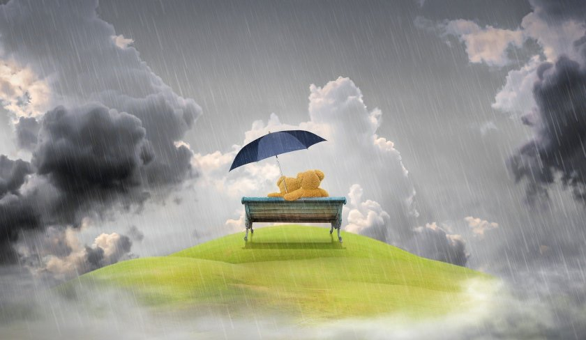 Two teddybears sheltering under an umbrella on a bench