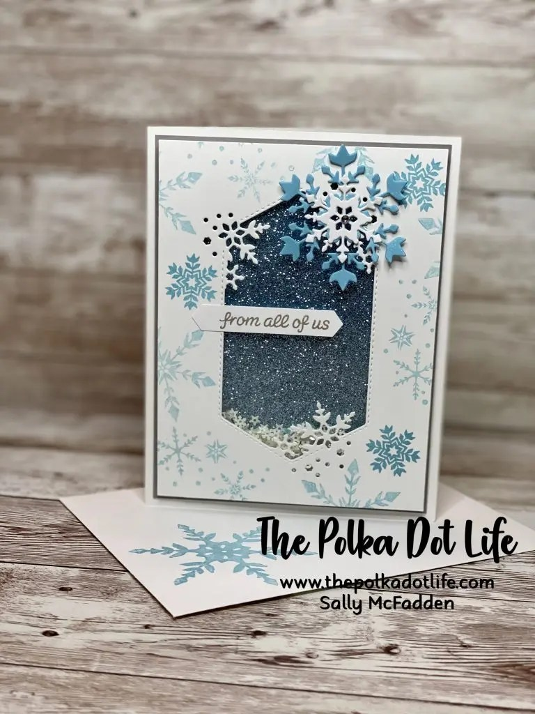 A white greeting card with snowflakes and sequins.  It was made using Stampin' Up products.