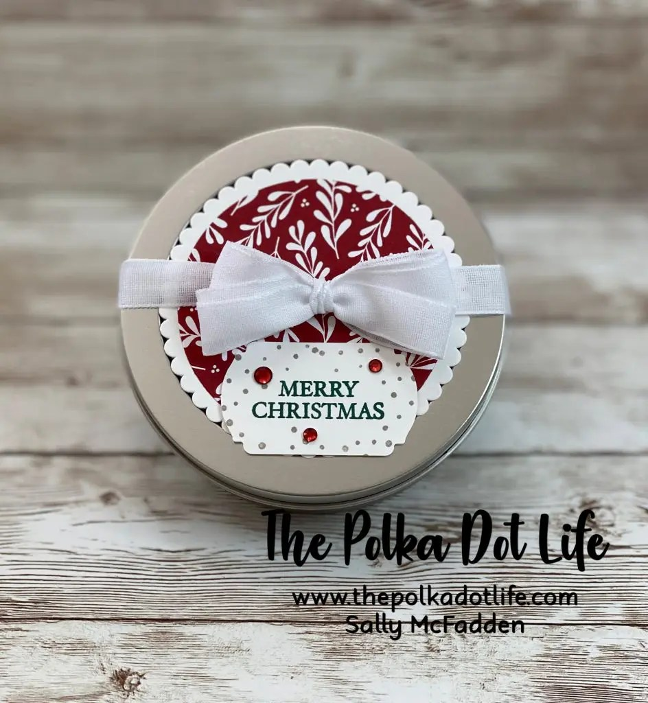 A gorgeous round gift tin.  It is decorated with Designer Series Paper from Stampin' Up.  It has a lovely white bow and a few sparkly gems.