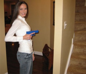 Amanda Hanson demonstrates how the gun should be close to the body before attempting to open a door. This helps to prevent someone from grabbing the gun out of your hands. Notice, she also has her finger off the trigger.