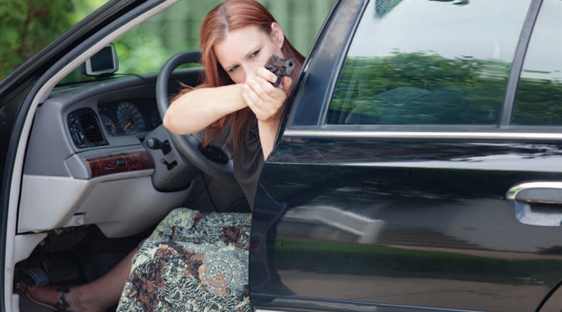 When shooting in or around vehicles, you may need to use unfamiliar or even awkward shooting positions. Here, the shooter steadies the back of her hand on the car's frame to help maintain her accuracy.