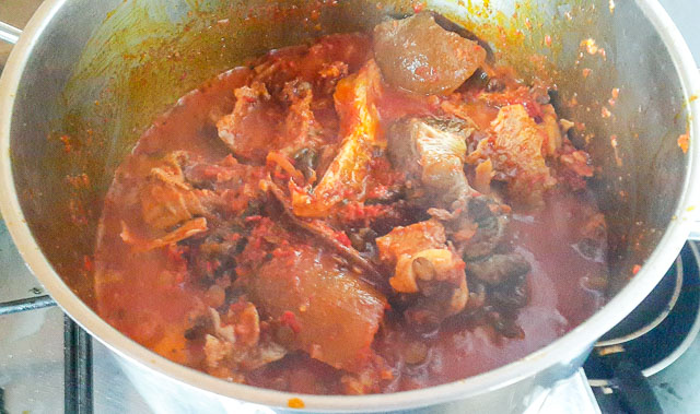 stew and meat in a pot for Efo riro (vegetable soup)