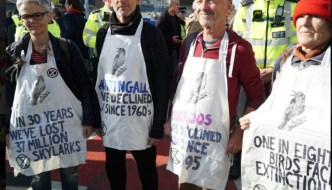 four people with slogan on their aprons at city airport