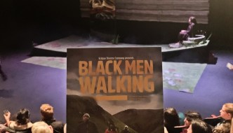 the Black Men Walking programme held up from the audience looking out over the rest of the audience to the stage