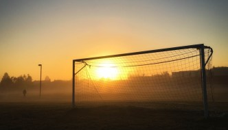a football goal at dusk with a jogger nearby