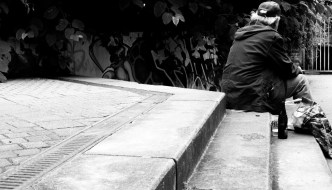 a black and white picture of a man sitting on steps with his back to us