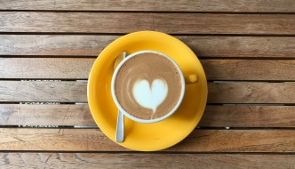 a cup of coffee with a milk heart on it