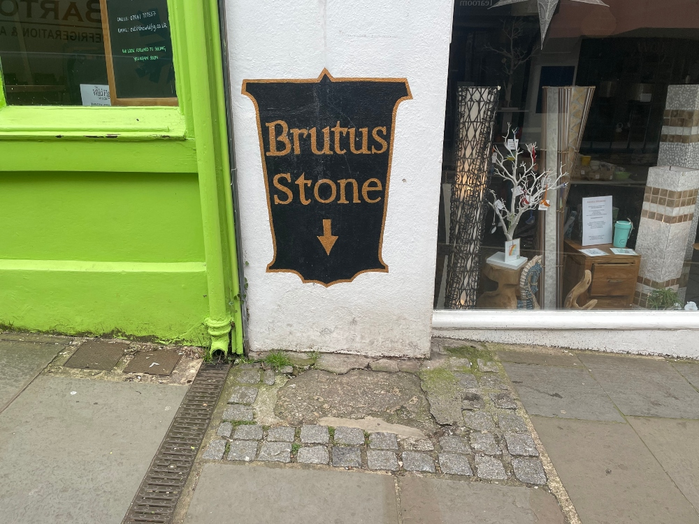 the brutus stone in Totnes - a plaque on a wall pointing to a piece of pavement