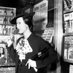 "Actress Anna May Wong poses for a photo in front of a magazine rack displaying the August 1934 number of ""Astounding Stories"" in Chicago."