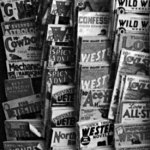 To make it easier to read the titles, we've flipped this photo of pulps hanging from a rack at a Manchester, N.H., shop in September 1937.