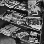 "Here's a mix of pulps, comic books, ""true detective"" magazines and other magazines on this rolling stand. On the bottom shelf is the first issue of ""Exiting Love"" (Winter 1941). Moving up, you'll see ""Planet Stories"" (Spring 1941), ""Amazing Stories"" (August 1941), and a bit of ""Astonishing Stories"" (August 1940)."