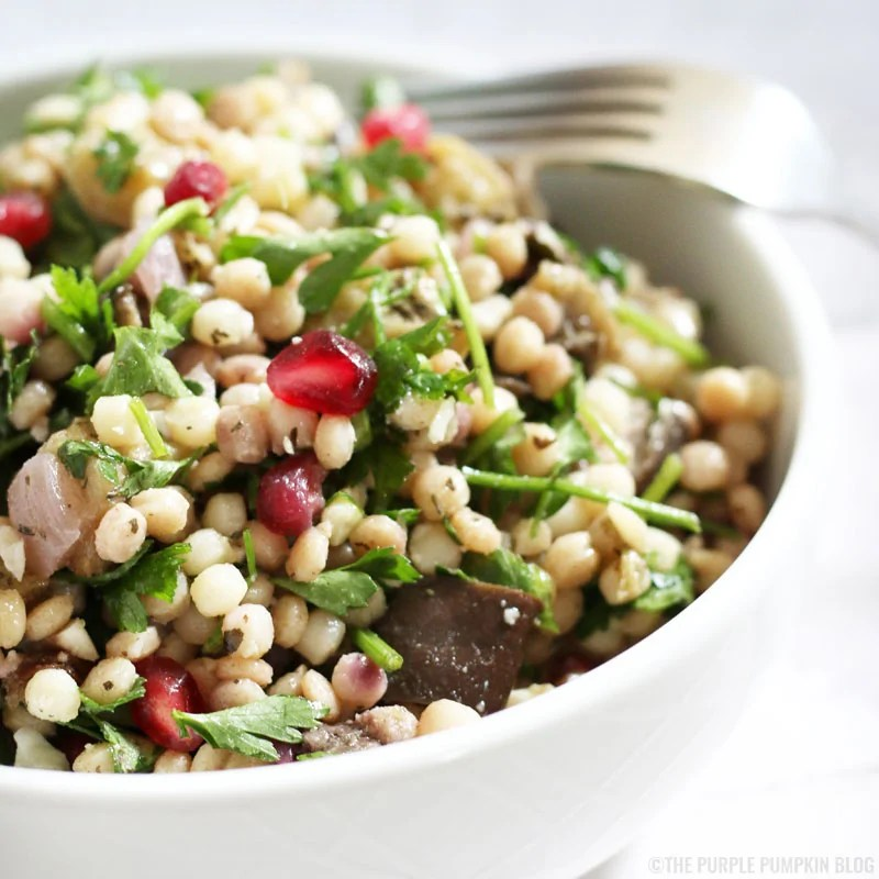 Giant Couscous Salad with roasted aubergine, parsley, and pomegranate.