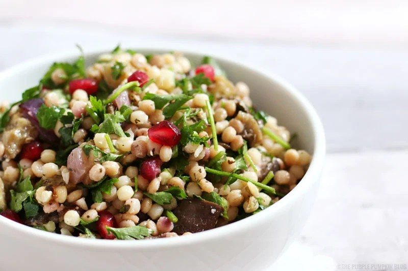 Giant Couscous Salad with roasted aubergine, parsley, and pomegranate. This salad is made using Middle Eastern flavours, and is great as a side dish with grilled meats, or as a meal on its own. It is a great salad to take to a potluck or a summer picnic, and can also be meal-prepped in Mason Jars for midweek lunches.