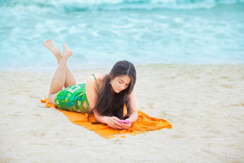 Teenage girl looking at mobile phone on the beach