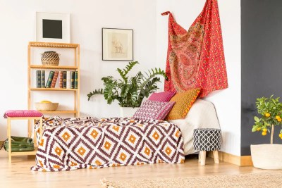 Boho Bedroom Decor Ideas with diamond patterned bed spread, mandala fabric print hanging on the wall, plants and books