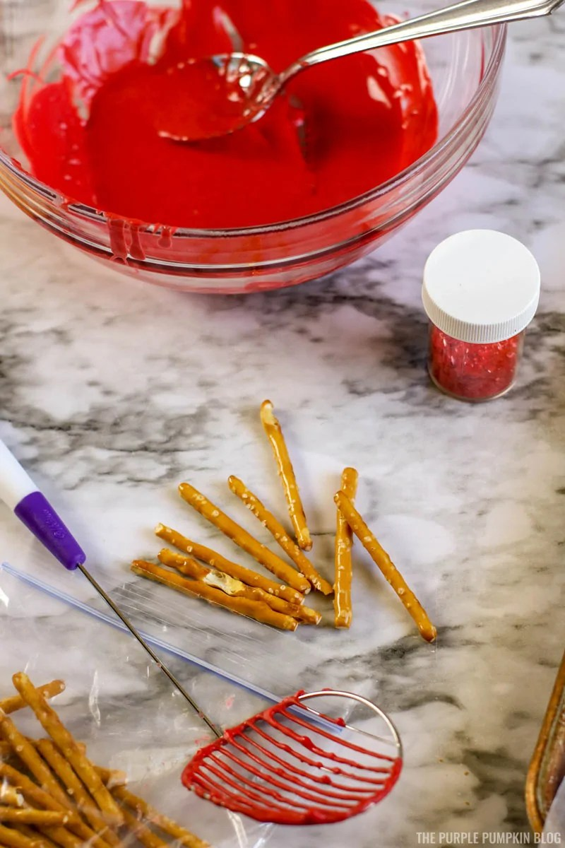 a bowl of melted red candy, with pretzel sticks for dipping