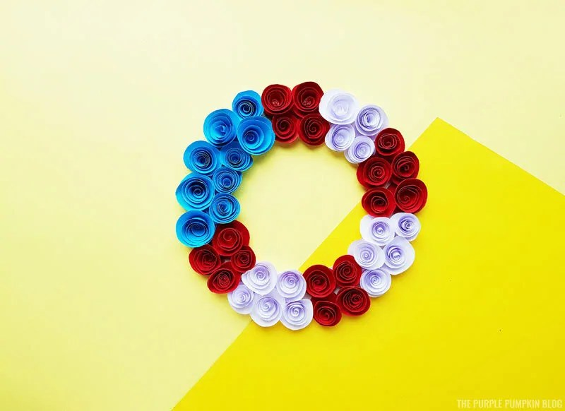 A red white and blue paper flower wreath on a yellow background.