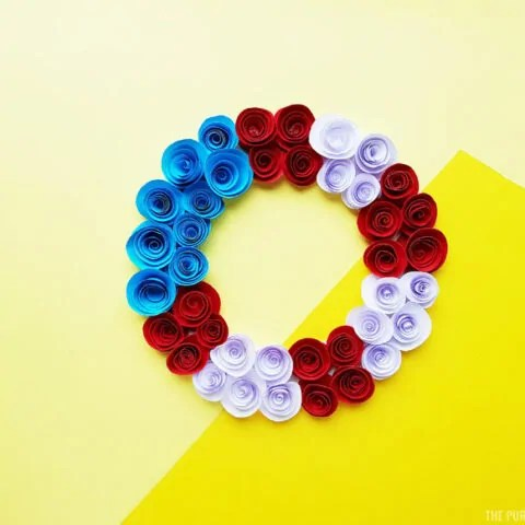 Red, white and blue wreath made with paper flowers on a yellow background