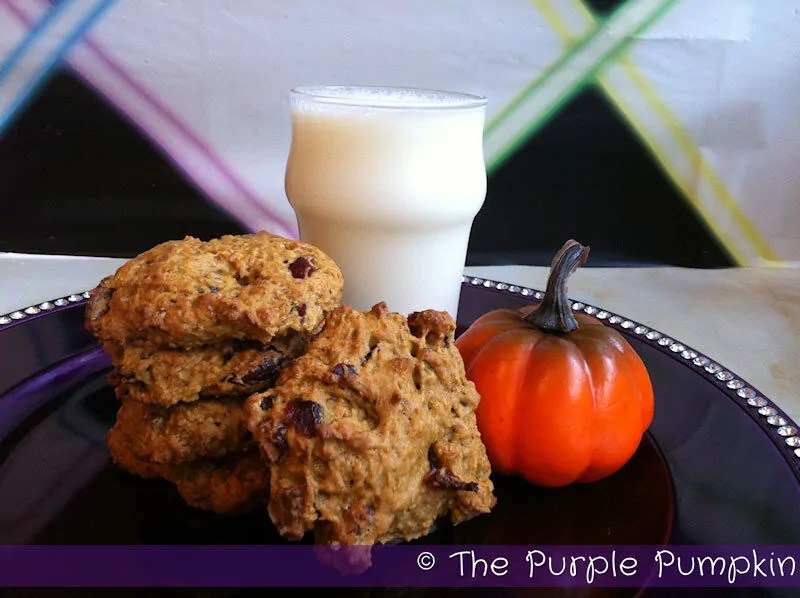 a plate of pumpkin cookies with a glass of milk