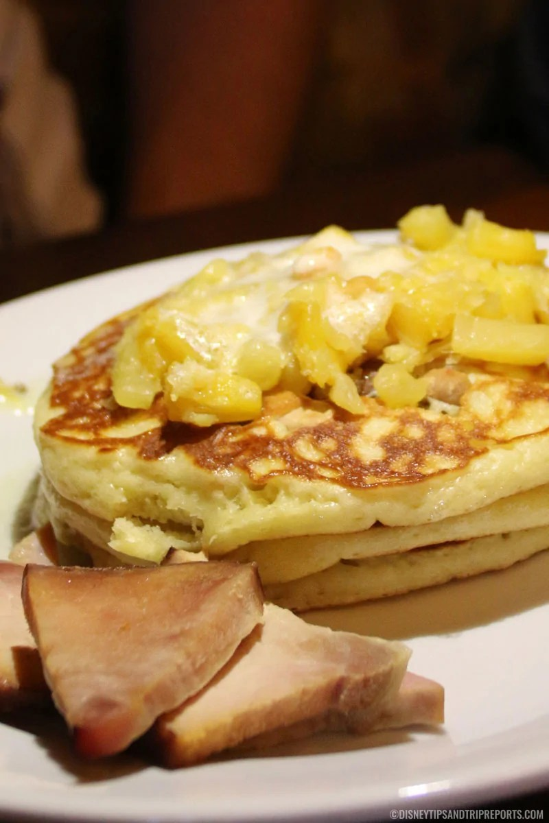 A stack of 3 pancakes topped with macadamia nut butter and pineapple, and a side of ham.