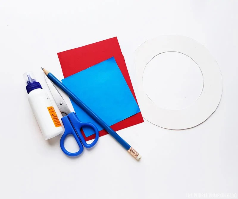 Craft supplies to make a paper flower wreath are laid out on a white background. They include red, white and blue paper, a pencil, scissors, and a tube of glue.