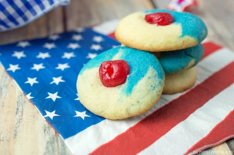 A stack of red, white, and blue cherry almond cookies on a paper napkin with a US flag design on it.