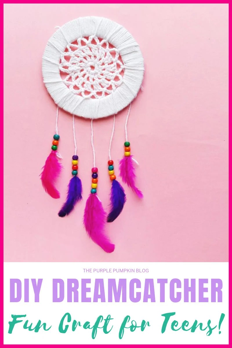 A DIY Dreamcatcher with pink and purple feathers on a pink background