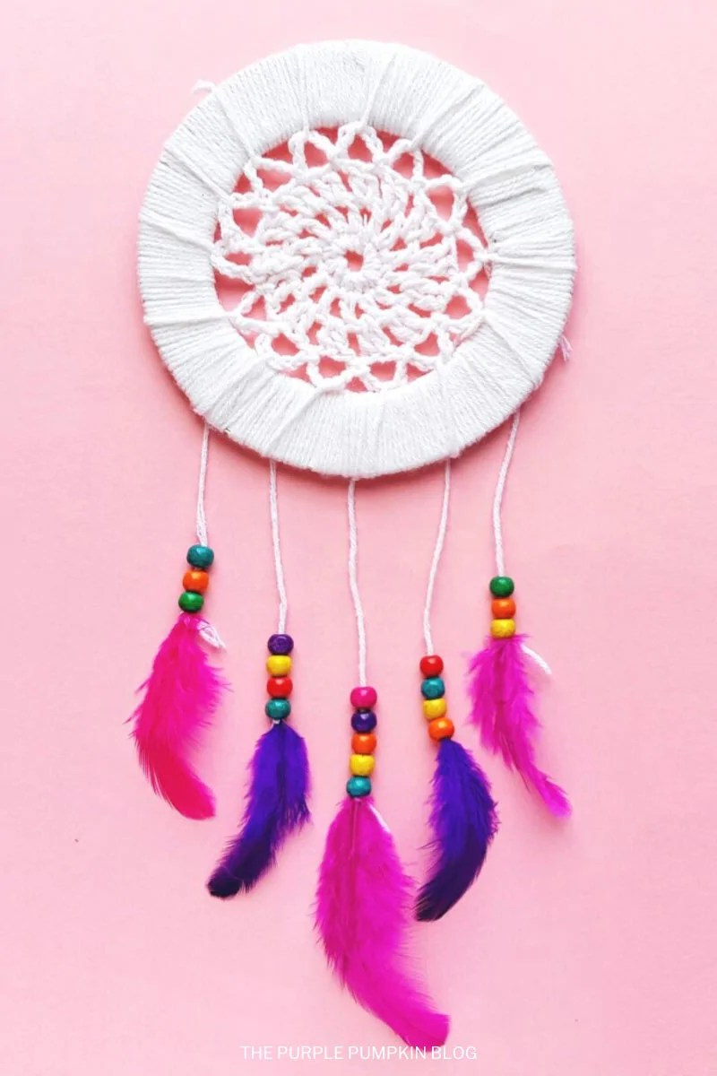 DIY Dreamcatcher with pink and purple feathers, multicolored beads on a pink background.