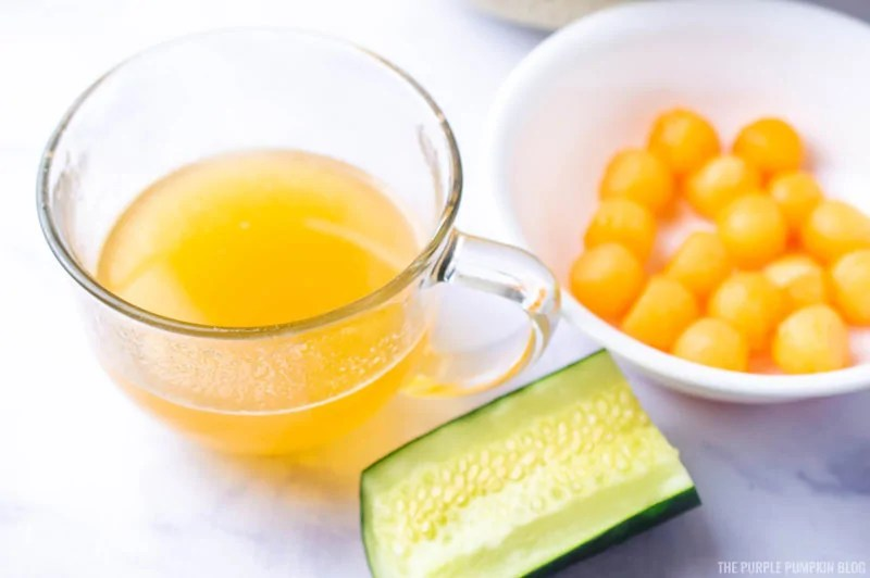 Melon Balls in a white bowl, with a glass of sugar syrup and half a cucumber