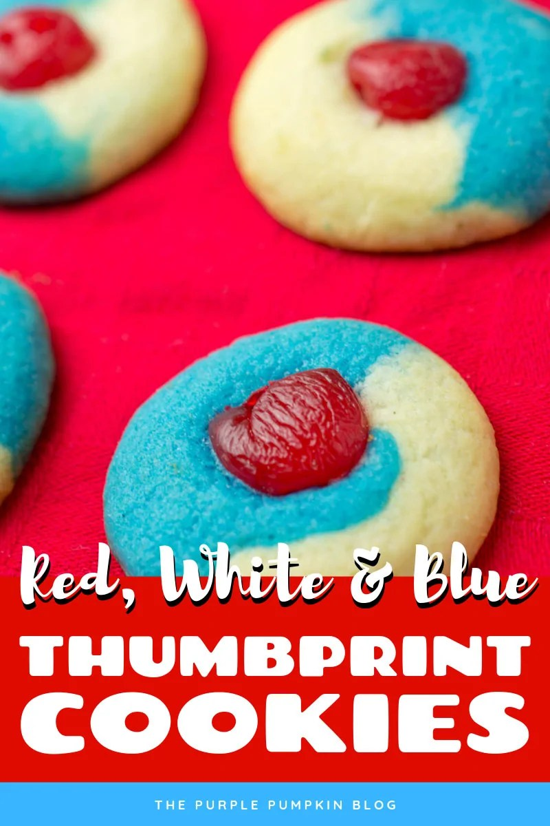 close up of red, white, and blue thumbprint cookies with a cherry on top, place on a red tablecloth.