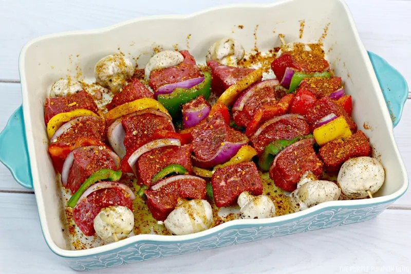 Prepped, raw steak kebabs in a dish.