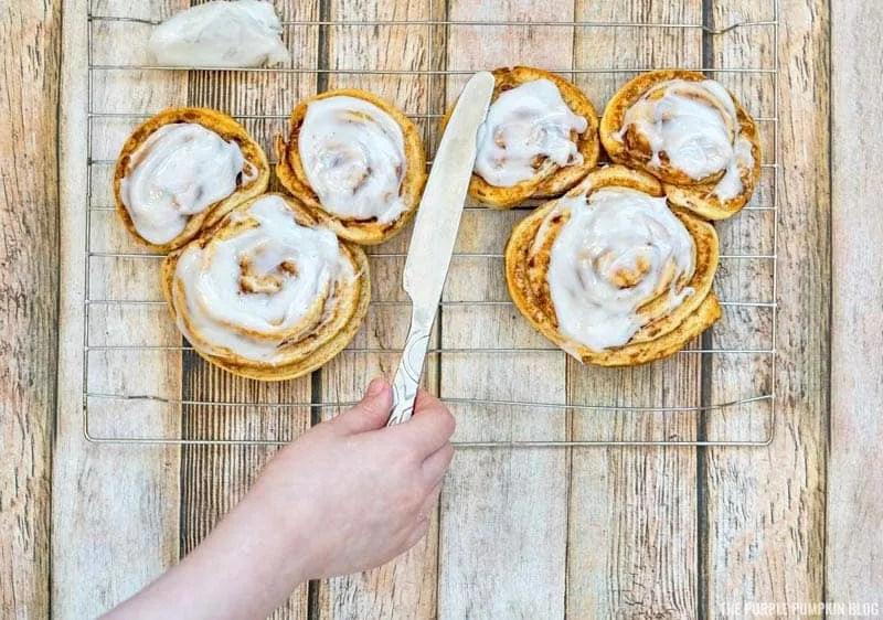 Spreading bake cinnamon rolls with icin