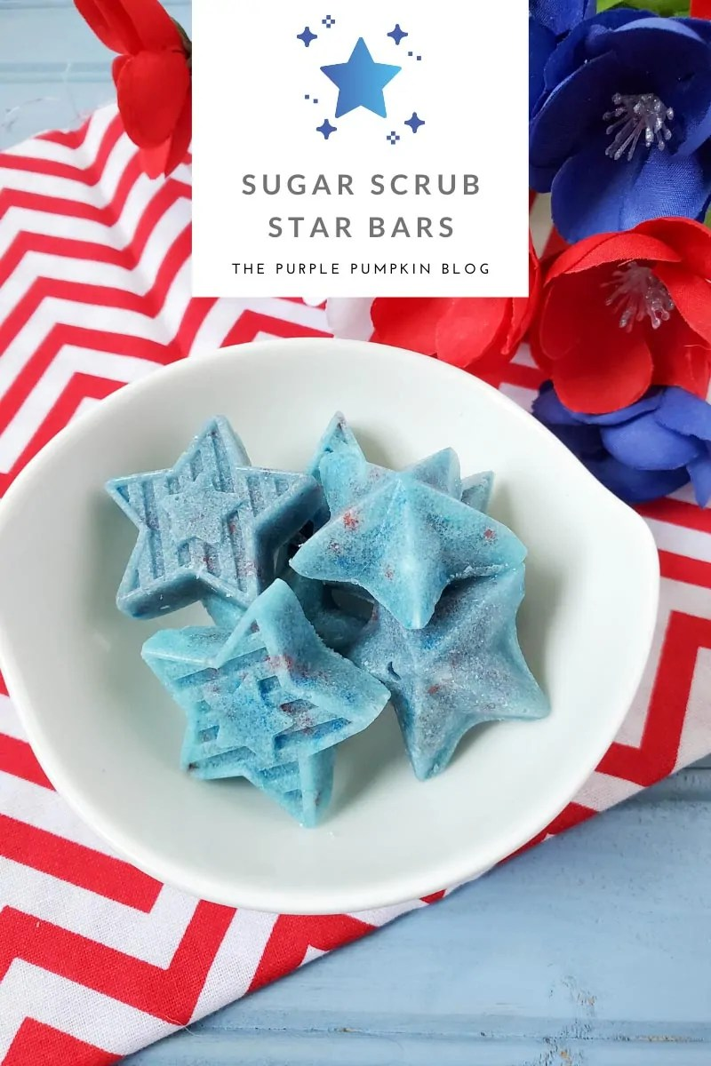 Blue Sugar Scrub Star Bars sitting in a white bowl on a red and white cloth with red, white and blue flowers in the background.