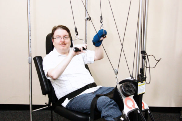 A full body passive/active therapy machine that moves all your limbs. Notice the grip assist glove on his left hand makes maintaining his grip easy. The machine is motorized and patterning helps to retrain the brain how to move again.